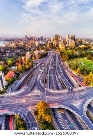 Wide multi lane Warringah freeway near North Sydney leading towards the Sydney Harbour bridge along high-rise business towers through residential suburbs in aerial vertical panorama. Royalty-Free Stock Photo #1526900399