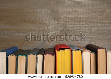 Stack of hardcover books on wooden background. Space for text #1526924780