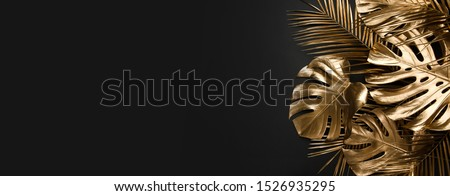 Golden monstera and date palm leaves creatively arranged on plain black background. Luxurious trendy border frame, shiny fashion botany flat lay concept. Floral natural wide horizontal decoration.
