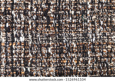 textile square background - interlacing of threads in motley boucle fabric close up