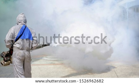 Rear view of outdoor healthcare worker in protective clothing using fogging machine spraying chemical to eliminate mosquitoes and prevent dengue fever at general location in community Royalty-Free Stock Photo #1526962682