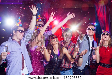Cheerful young people showered with confetti on a club party. #1527035324