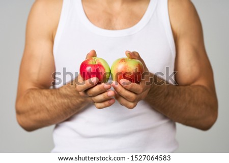 young man in a white t-shirt holds apples in his hands #1527064583