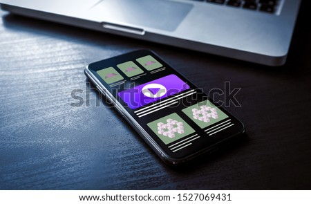 Responsive website design concept, mobile web usability. Closeup smartphone with adaptive ui/ux web page design on wooden table and with a laptop in the background #1527069431