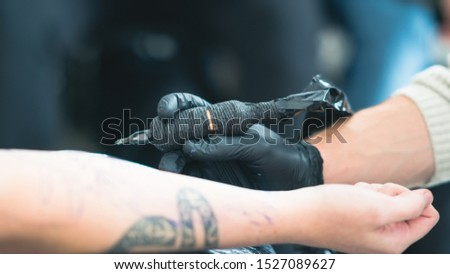 Professional tattoo artist makes a tattoo on a young man's hand, close-up. Master doing tattoo in salon. Process of making tattoo in studio. #1527089627