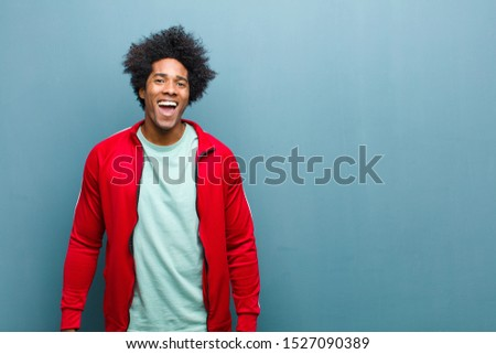 young black sports man with a big, friendly, carefree smile, looking positive, relaxed and happy, chilling against grunge wall #1527090389