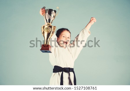 Girl little child in white kimono with belt. Karate fighter child. Karate sport concept. Self defence skills. Karate gives feeling of confidence. Strong and confident small kid. Victory and win. #1527108761