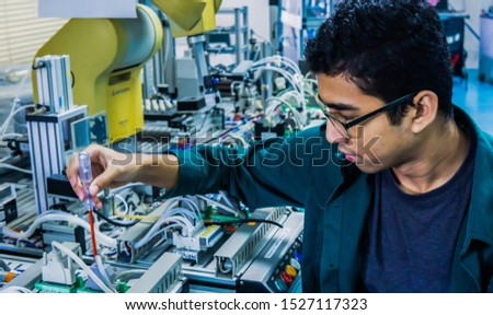 A young Malay engineering student with spectacles working in the lab repairing and troubleshooting an automation machine system using a screwdriver. Image contain noise reduction. Selected focus. #1527117323