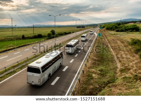 Caravan or convoy of Four buses in line traveling on a highway country highway #1527151688