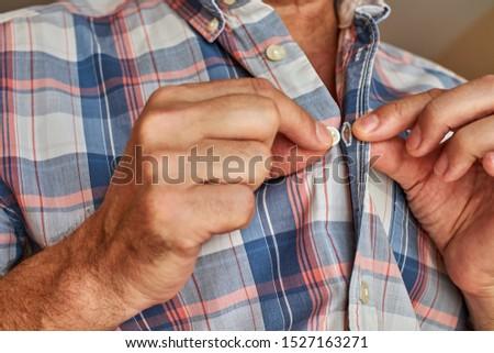 man buttoning up plaid shirt button #1527163271