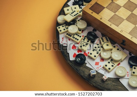 Various board games chess board, playing cards, dominoes on a old wooden table orange background.