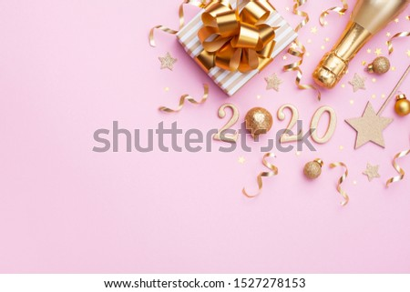 Flat lay background for Christmas and New Year. Champagne bottle, golden gift or present box, 2020 number and confetti on pink top view.  #1527278153