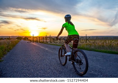 Beautiful girl cyclist rides a bicycle on the road in the sunset. Healthy lifestyle and sport. Leisure and hobbies #1527294404