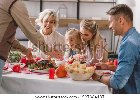 family members sitting at table and grandfather holding plate with turkey in Thanksgiving day       #1527364187