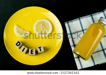 Bottle of fresh orange juice with slice fresh lemon on yellow plate. Creative food or diet food and creative pic