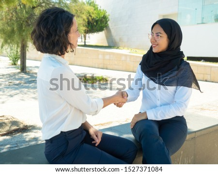 Businesswoman dealing with Muslim colleague outside. Business women sitting near office building, talking and shaking hands. Deal concept #1527371084