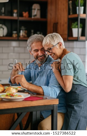 Happy mature couple during lunchtime together at home #1527386522