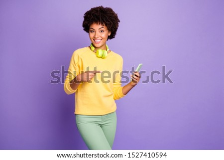 Photo of wavy trendy stylish trendy cheerful positive cute sweet girlfriend wearing green pants trousers yellow sweater smiling toothily pointing at her phone with headphones isolated violet color #1527410594