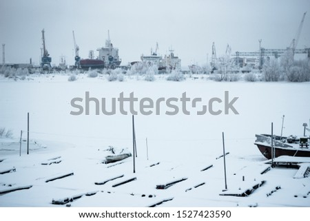 The ships, cranes and water vessels are frozen in the port. Winter cold day at the river port. Gray sky and frozen river. Everything is covered with snow #1527423590