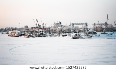 The ships, cranes and water vessels are frozen in the port. Winter cold day at the river port. Gray sky and frozen river. Everything is covered with snow #1527423593