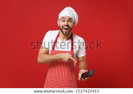 Laughing young bearded male chef cook or baker man in striped apron toque chefs hat isolated on bright red background. Cooking food concept. Mock up copy space. Pointing index finger on mobile phone #1527425411