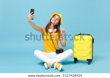 Traveler tourist woman in yellow casual clothes hat with suitcase photo camera isolated on blue background. Female passenger traveling abroad travel on weekends getaway. Air flight journey concept #1527428924