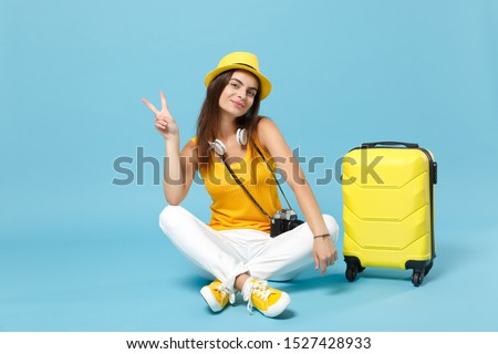 Traveler tourist woman in yellow casual clothes hat with suitcase photo camera isolated on blue background. Female passenger traveling abroad to travel on weekends getaway. Air flight journey concept #1527428933