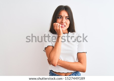Young beautiful woman wearing casual t-shirt standing over isolated white background looking stressed and nervous with hands on mouth biting nails. Anxiety problem. #1527449189