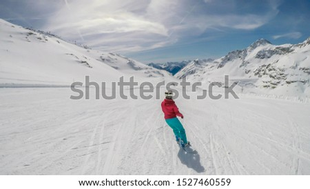 A snowboarder going down the slope in Mölltaler Gletscher, Austria. Perfectly groomed slopes. High mountains surrounding the girl wearing colourful snowboard outfit. Girl wears helm for the protection #1527460559