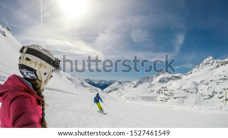 A snowboarding girl and skiing man going down the slope in Mölltaler Gletscher, Austria. Perfectly groomed slopes. High mountains surrounding the couple. They wear helm for the protection. Active life #1527461549