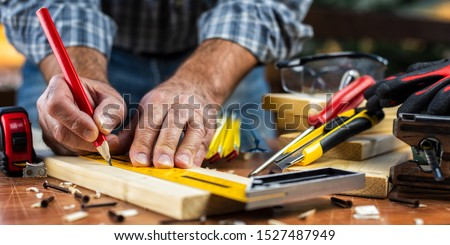 Adult carpenter craftsman with a pencil and the carpenter's square trace the cutting line on a wooden table. Construction industry, housework do it yourself. Stock photography. #1527487949