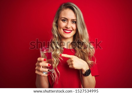 Young beautiful woman drinking a glass of water over red isolated background very happy pointing with hand and finger