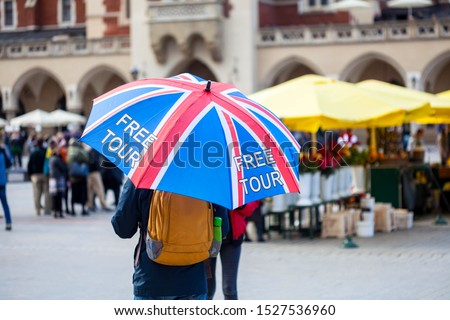 Free tour on a Cracow market square, a UK english guide with a united kingdom flag umbrella seen from the back. Local free of charge tourist guides. Tourism, travelling for england residents concept #1527536960