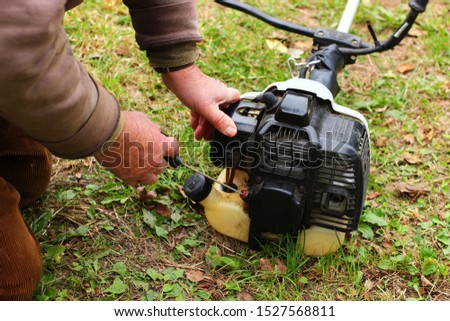 A man runs the motor of gasoline trimmer #1527568811