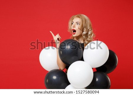 Shocked young woman girl in black clothes posing isolated on red background. Women's Day birthday holiday party concept. Mock up copy space. Celebrating hold air balloons pointing index finger aside #1527580094