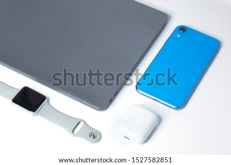 Still life, composition of new modern gadgets, devices: sport smartwatch, wireless earphones in case, blue cell mobile smartphone and grey laptop. Technology concept. Flat lay. White background. #1527582851