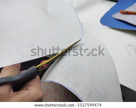 In a woman's hand scissors. Cutting patterns for sewing clothes. Close-up photo. #1527599474