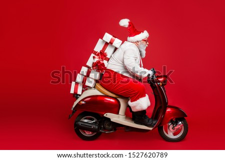 Profile side view portrait of nice bearded funny funky purposeful Santa Claus riding moped hurry up delivering pile stack shop purchases isolated on bright vivid shine vibrant red color background #1527620789