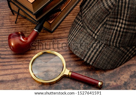 Literary fiction, police inspector, investigate crime and mystery story conceptual idea with sherlock holmes detective hat, smoking pipe, retro magnifying glass and book isolated on wood table top #1527641591
