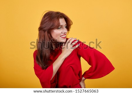 Gorgeous European woman touching her left shoulder with right hand. Beautiful lady in reddish clothes with reddish lips standing over isolated background. #1527665063