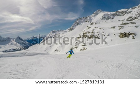 A skier going down the slope in Mölltaler Gletscher, Austria. Perfectly groomed slopes. High mountains surrounding the man wearing yellow trousers and blue jacket. Man wears helm for the protection. #1527819131