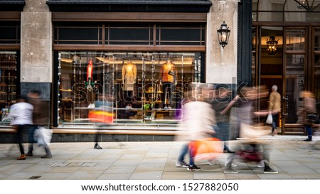 Motion blurred people on busy shopping street Royalty-Free Stock Photo #1527882050