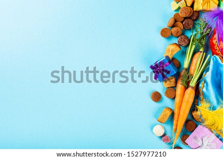 St. Nicholas Day background. Card. Dutch holiday Sinterklaas flat lay with gifts, pepernoten, traditional sweets strooigoed. Holiday greeting card with copy space. #1527977210