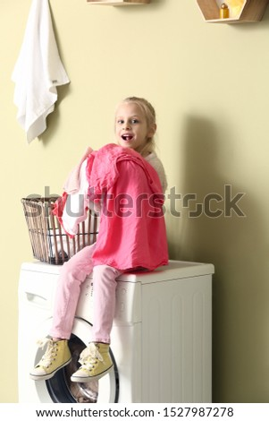 Little girl with laundry sitting on washing machine at home #1527987278