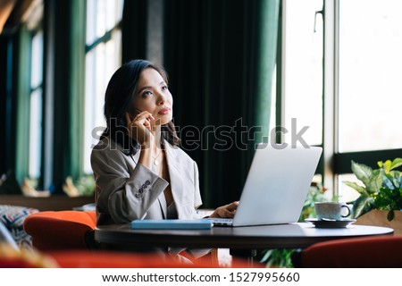 Portrait of kazakh young and successful woman solving business problems during phone conversation sitting in modern coffee shop. Pretty  interior is enjoying of her free time in cafe.  #1527995660