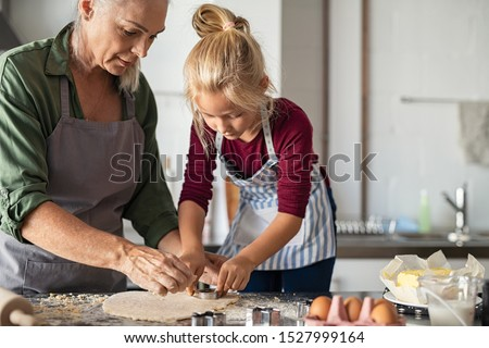 Grandmother and granddaughter using cookie cutter to cut dough in shapes. Little cute girl and senior grandma in apron preparing cookies for christmas. Grandchild with old granny cooking in kitchen.  #1527999164