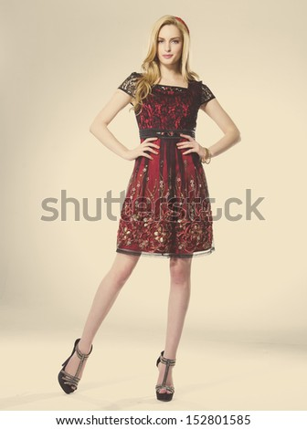 young girl standing in elegant dress against gold background  #152801585