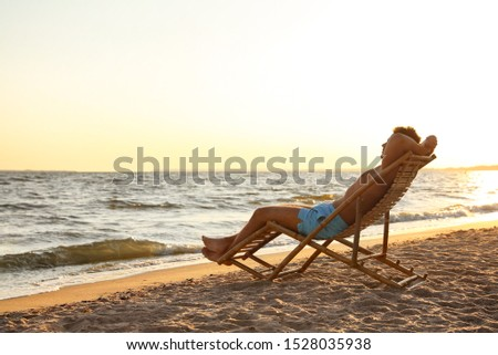 Young man relaxing in deck chair on beach near sea #1528035938