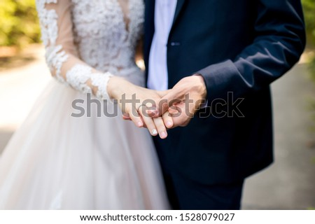 Hands with wedding rings. Groom and bride photosession. Closeup. #1528079027