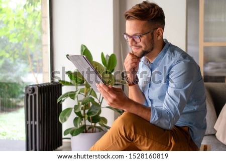 Young smiling Man typing on digital tablet #1528160819